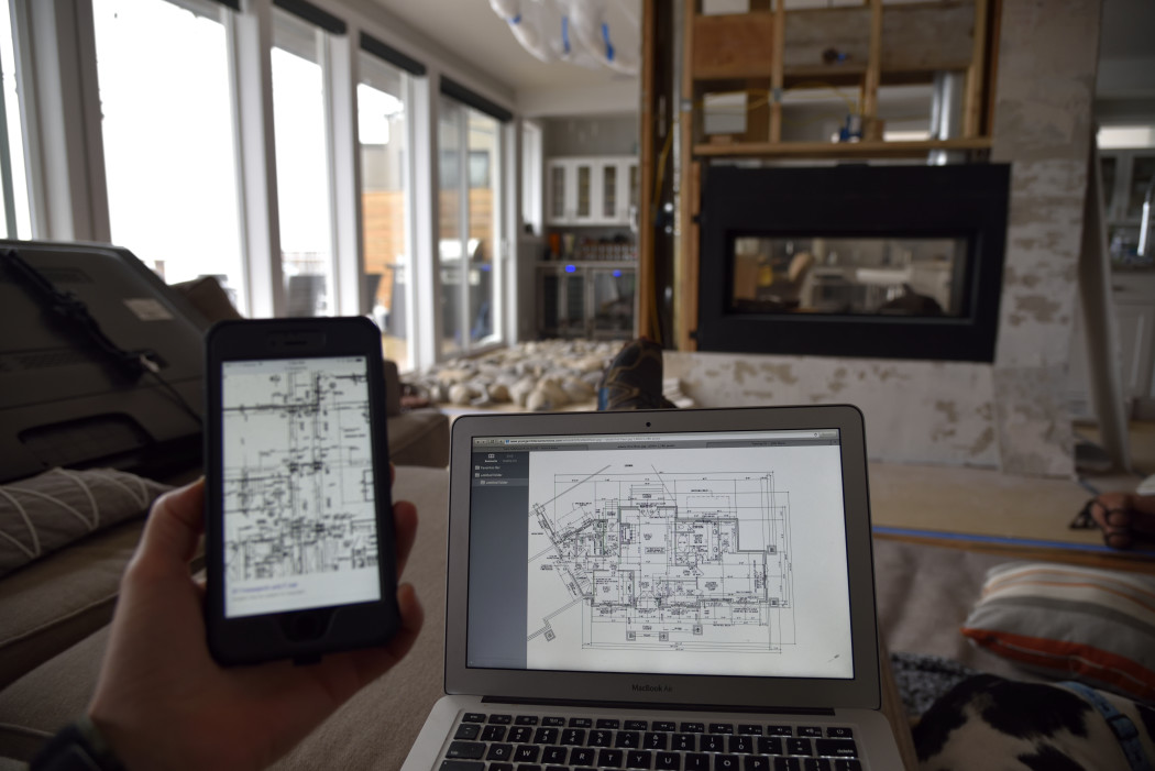 contractor looking at his blueprints on a laptop and cellphone