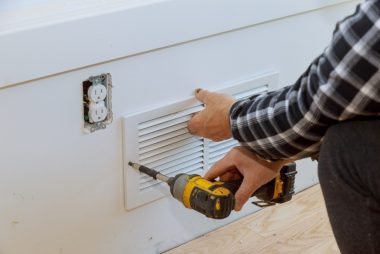 man installing a wall ventilation cover